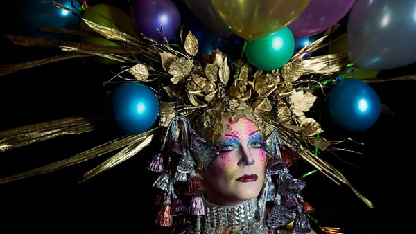 A headshot of a person with an elaborate head piece of golden flora and multicolored balloons, and brightly colored stage makeup